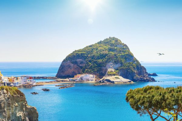 Panoramic view of giant rock with green trees on top near small village Sant'Angelo on Ischia island, Italy